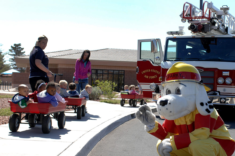 Sparky the Fire Dog, with fire appliance and a group of small children